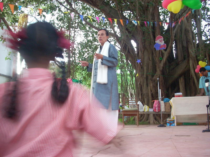 Photographer:Andrea | Domique conducting the choir under the Banyam tree