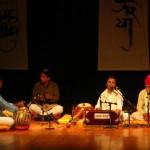 Hemant Chauhan sings and plays harmonium while hosting Prahlad Tipanya on stage
