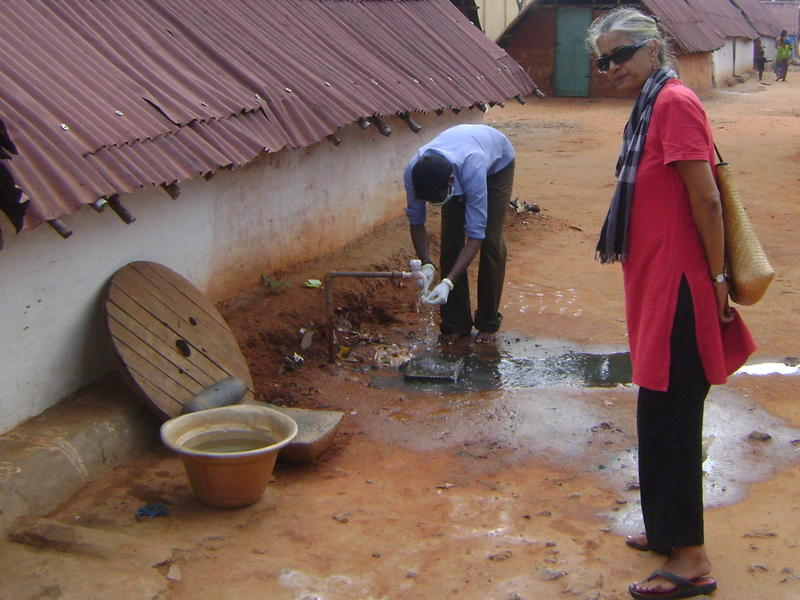 Photographer:Herman | Sham cleaning the sludge of his hands with Renu standing by.