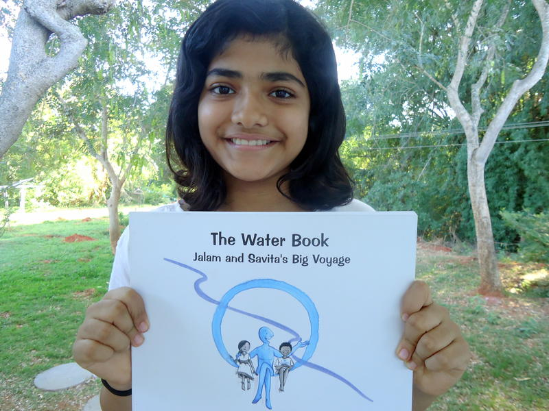 Photographer:Sandrine | Ahilya with the hard copy of the Water Book.