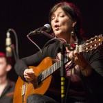Shakti plays her guitar and sings